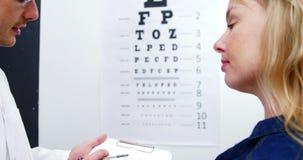 Optometrista que discute informe de prueba del ojo del paciente femenino metrajes