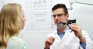 Optometrista que discute sobre messbrille con el paciente femenino almacen de metraje de vídeo