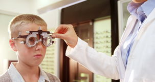 Optometrista que examina al paciente joven con el chiropter metrajes