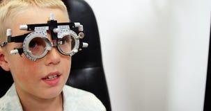 Optometrista que examina al paciente joven con el chiropter almacen de metraje de vídeo