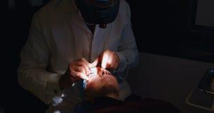 Optometrista que examina ojos pacientes con el equipo de prueba del ojo en la clínica 4k metrajes