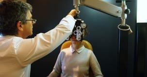 Optometrista que examina ojos pacientes con el messbrille 4k metrajes