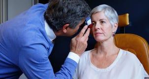 Optometrista que examina ojos pacientes con el oftalmoscopio 4k almacen de metraje de vídeo