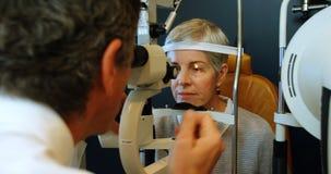 Optometrista que examina ojos pacientes con la lámpara rajada 4k metrajes