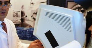 Optometrista que examina ojos pacientes con los autorefractors 4k almacen de metraje de vídeo