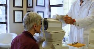 Optometrista que examina ojos pacientes con los autorefractors 4k almacen de video