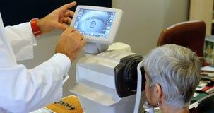 Optometrista que examina ojos pacientes con los autorefractors 4k metrajes