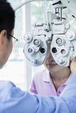 Optometrista que faz um exame de olho na jovem mulher Imagens de Stock Royalty Free