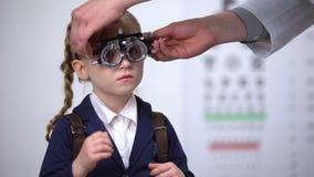 Optometrista que pone el marco de ensayo óptico en colegiala para determinar agudeza visual metrajes