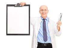 Optometrista que sostiene vidrios y un tablero Imagenes de archivo