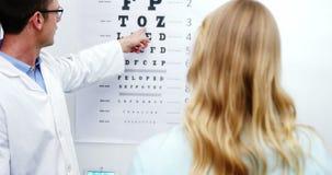 Optometrista que toma la prueba del ojo del paciente femenino metrajes