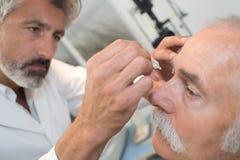 Optometrista que usa descensos de ojo del mydriatics para entumecer ojos Fotos de archivo