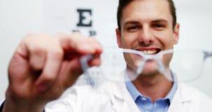Optometrista sonriente que sostiene gafas almacen de video