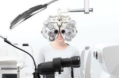 Optometristexamen, de patiënt van de zichtvrouw met phoropter in opti stock afbeelding