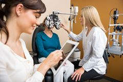 Optometrists Examining Senior Woman In Store. Female optometrist examining senior woman's eyes while colleague using digital tablet in store Royalty Free Stock Photography