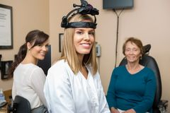 Optometrists With Senior Patient In Store. Portrait of female optometrists wearing binocular indirect ophthalmoscope Stock Photo