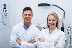 Optometrists standing in ophthalmology clinic. Portrait of optometrists standing with arms crossed in ophthalmology clinic Stock Photography