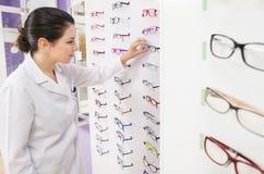 Optometristvrouw die haar glazen kijken Stock Fotografie