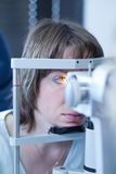 Optometry concept. Pretty young woman having her eyes examined by an eye doctor Royalty Free Stock Photo