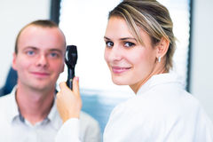 Optometry concept - handsome young man having his eyes examined Stock Photography