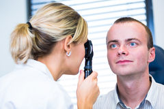 Optometry concept - handsome young man having his eyes examined Royalty Free Stock Images