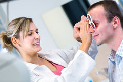 Handsome young man having his eyes examined Royalty Free Stock Photography