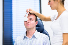 Handsome young man having his eyes examined Stock Image