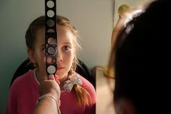 Optometry concept - medical doctor with magnifier examining little girl stock photos