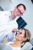 Optometry concept - pretty young woman having her eyes examined Stock Photography