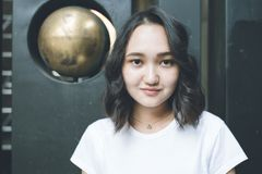 Optymistycznie azjatykcia dziewczyna w białej koszulce, miastowy portrat zdjęcie royalty free
