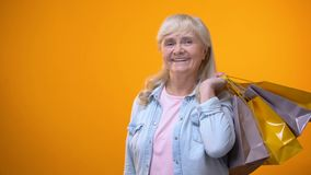 Optymistycznie starsza dama pokazuje torby na zakupy i euro banknoty, konsumeryzm zbiory