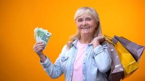 Optymistycznie starsza dama pokazuje torby na zakupy i euro banknoty, konsumeryzm fotografia stock