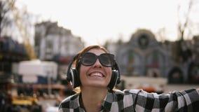 Optymistycznie, szczęśliwy dziewczyny odprowadzenie na ulicie, i słucha dobra muzyka w hełmofonach Jest roześmiana i taniec zbiory