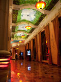 Opulent corridor with marble floor and curtains. Luxury corridor with marble floor, decorated, ceiling  wall, curtains, and chandeliers with ample light Royalty Free Stock Photography