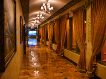 Opulent corridor with marble floor and curtains. Luxury corridor with marble floor paintings on the wall, curtains, and chandeliers with ample light Stock Photo