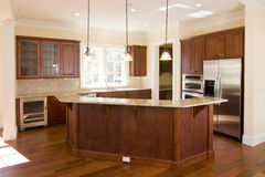 Opulent kitchen in dark wood. Opulent kitchen with dark wood and stainless appliances Royalty Free Stock Images