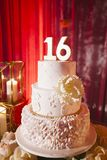 Opulent Sweet 16 cake. Ornate white cake for sweet 16 party with red backdrop stock photos