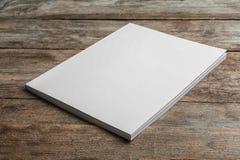 Opuscolo con la copertura in bianco su fondo di legno fotografia stock