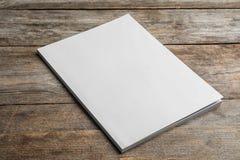 Opuscolo con la copertura in bianco su fondo di legno immagine stock