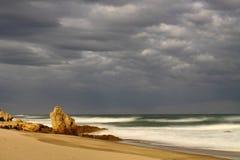 Opustoszała piaskowata plaża z ciemnym chmurnym niebem Zdjęcia Royalty Free