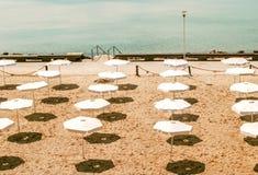 Opustoszała plaża z białymi parasolami Zdjęcia Royalty Free