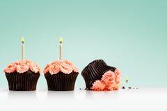 Opuszczająca babeczka w rzędzie babeczki z świeczkami na zieleni Zdjęcia Stock