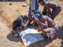 Opuwo, Namibia - 25. Juli 2015: Gruppe Männer und Jungen Himba, die sich vorbei lehnen und Karte von Namibia betrachten stockbild