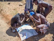 Opuwo, Namibia - July 25, 2015: Group of Himba men and boys leaning over and looking at map of Namibia stock image