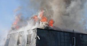 Opvlammende huisbrand, het water van de brandbestrijdersnevel op dak met slang stock footage