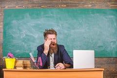 Opvoeder gebaard die mens geeuwgezicht op het werk wordt vermoeid De opvoeders beklemtoonden meer op het werk dan gemiddelde mens stock fotografie