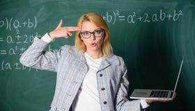Opvoeder slimme slimme dame met het moderne laptop gebaar van het greepkanon bij haar hoofdbordachtergrond Vermoeide geërgerde le royalty-vrije stock fotografie