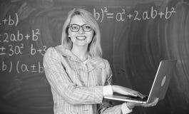 Opvoeder slimme slimme dame met moderne laptop die de achtergrond van het informatiebord zoeken De slijtageoogglazen van de vrouw royalty-vrije stock foto's