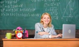 Opvoeder van de leraars zit de vrolijke prettige vrouw het werk van het lijstklaslokaal met laptop Het leraars gelukkige werk in  royalty-vrije stock afbeelding