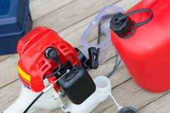 opvullend met brandstof van een rode bus met benzine, handgrasmaaimachineclose-up, op een houten achtergrond stock afbeelding